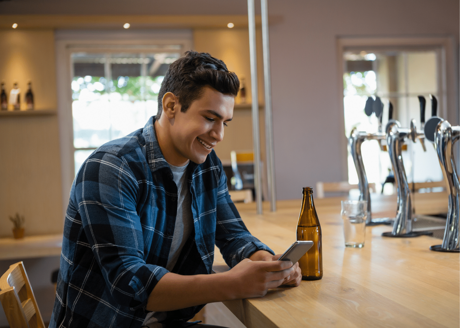 guy in plaid shirt smiling at cell phone